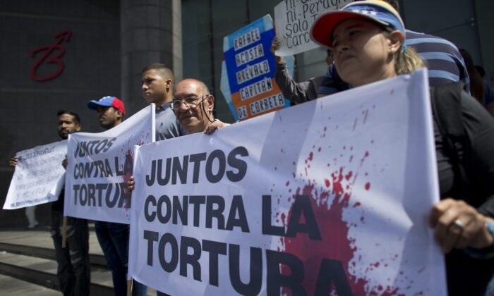 "Opposition activists hold a banner that reads in Spanish ""Together against torture"" during a protest outside the United Nations Development Programme office in Caracas, Venezuela on July 15, 2019. (Ariana Cubillos/The Associated Press)"