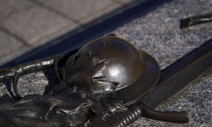 A bronzesmith restored the helmet on the Tomb of the Unknown Soldier at the National War Memorial in Ottawa Oct. 17, 2020, after it was vandalized on Oct. 16. (The Canadian Press/Justin Tang)