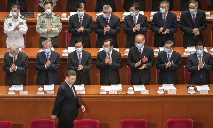 Chinese president Xi Jinping is applauded by delegates wearing protective masks as he arrives at the opening of the National People's Congress at the Great Hall of the People in Beijing, China on May 22, 2020. (Kevin Frayer/Getty Images)