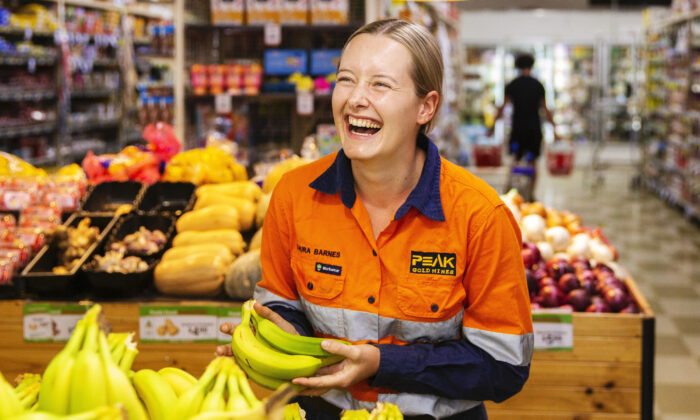 Cobar local Laura Barnes laughs as she picks bananas at Khan's Supa IGA in Cobar Australia on April 17, 2020. (Jenny Evans/Getty Images)