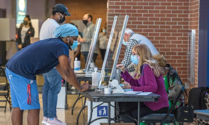 A poll worker assists a voter at the Spectrum Center, during the first day of early voting in Charlotte, N.C., on Oct. 15, 2020. (Grant Baldwin/AFP via Getty Images)