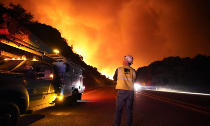 A Pacific Gas and Electric worker looks up at the advancing Creek Fire along Highway 168 near Alder Springs, Calif., on Sept. 8, 2020. (Marcio Jose Sanchez/AP Photo)