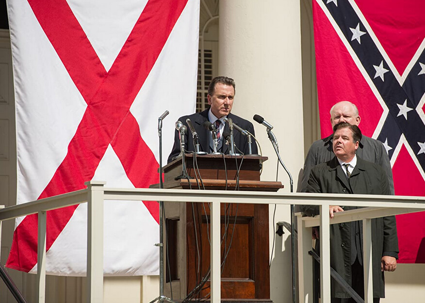 """man standing at podium in front of Rebel flag in """"Selma"""""""