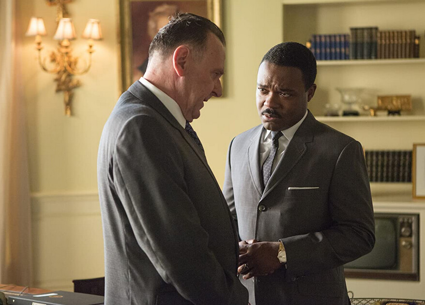 """Two men in grey suits stand in front of bookshelf in """"Selma"""""""
