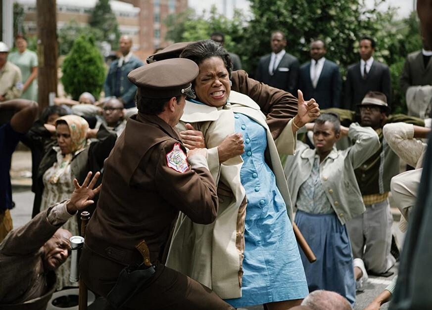 "woman in blue dress getting arrested by cops in ""Selma"""