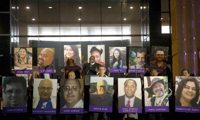 San Bernardino County employees hold up photos of the San Bernardino shooting victims during a candlelight vigil in San Bernardino, Calif., on Dec. 7, 2015. (AP Photo/Jae C. Hong, File)