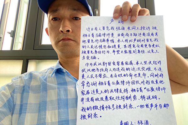 Zhang Hai, son of a COVID-19 victim, poses with a handwritten statement on Aug. 20, 2020. (Provided to The Epoch Times)