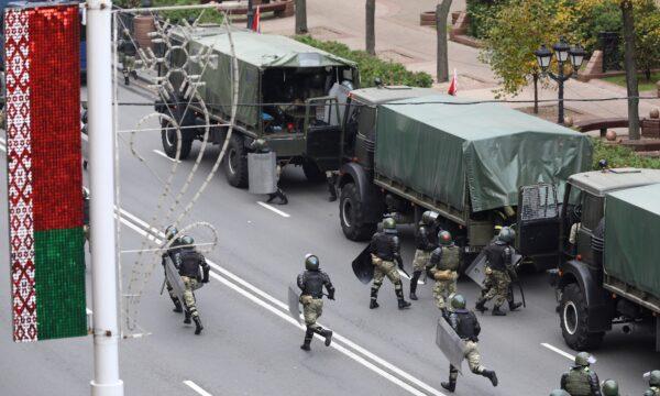 Belarusian law enforcement officers are seen near trucks