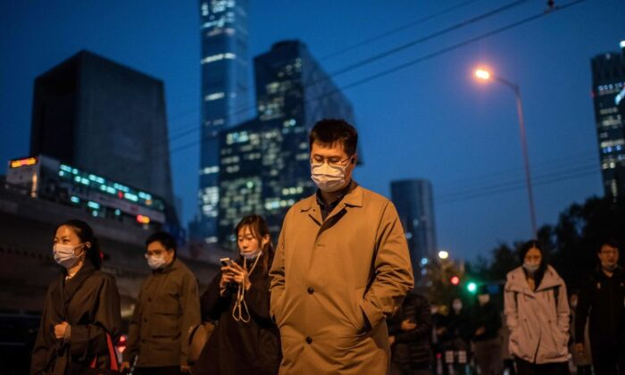 People wearing masks cross a street in Beijing on Oct. 21, 2020. (Nicolas Asfouri/AFP via Getty Images)