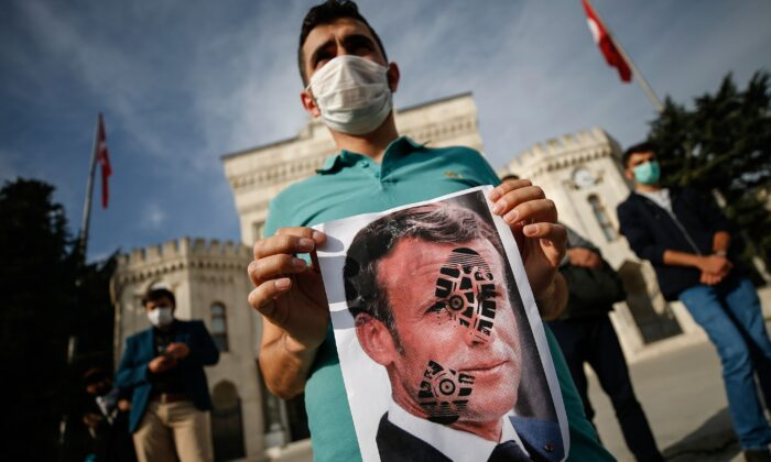 A Turkish man holds a photograph of France's President Emmanuel Macron, stamped with a shoe mark, during a protest against France in Istanbul, on Oct. 25, 2020. (Emrah Gurel/AP Photo)