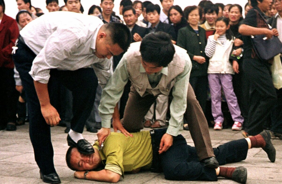 Police detain a Falun Gong protester in Tiananmen Square as a crowd watches in Beijing in this Oct. 1, 2000 photo. Falun Gong followers have tried mass phonings, street demonstrations and hijacking satellite signals to protest their persecution at the hands of Chinese authorities. But they're now taking a legal approach, filing at least 12 lawsuits in countries as the United States, Finland, and Australia against Chinese officials they accuse of perpetrating human rights abuses, from former president Jiang Zemin down. (AP Photo/Chien-min Chung)