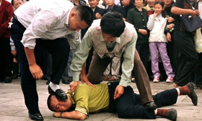 Police detain a Falun Gong protester in Tiananmen Square as a crowd watches in Beijing on Oct. 1, 2000. (Chien-min Chung/AP Photo)