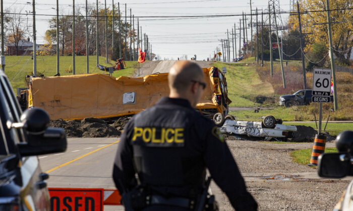 Ontario Provincial Police stand near a blockade on Argyle St. South in Caledonia, Ont., after a judge granted a permanent injunction against a land reclamation camp known as 1492 Land Back Lane, on Oct. 23, 2020. (The Canadian Press/Tara Walton)
