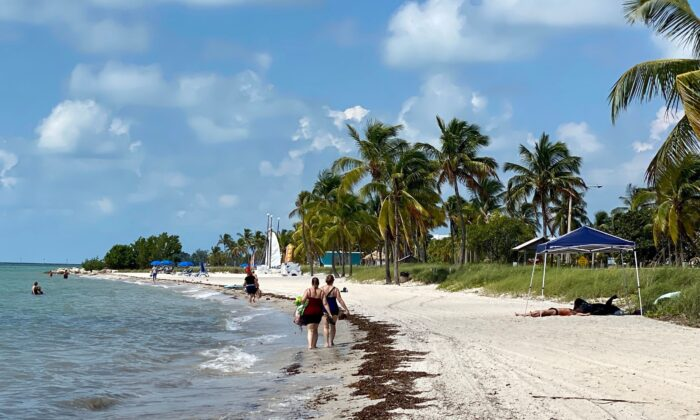 People walk along the shoreline of Key West Beach, Florida, on Sept. 18, 2020. Many snowbirds will not be travelling south this winter due to COVID-19 border restrictions. (Daniel Slim/AFP via Getty Images)