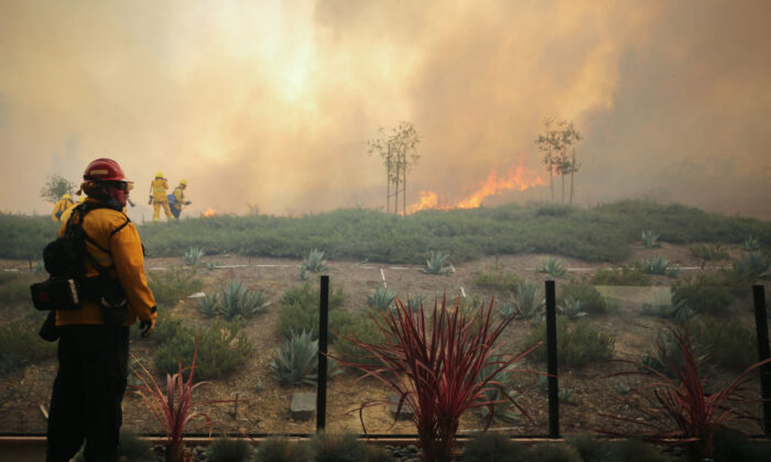 A firefighter works as the Silverado Fire burns toward a home in Orange County in Irvine, Calif., on Oct. 26, 2020. (Mario Tama/Getty Images)