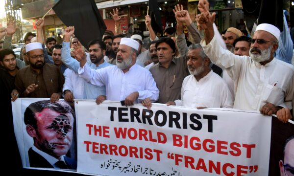 Pakistan traders hold a banner with a defaced picture of French President Emmanuel Macron