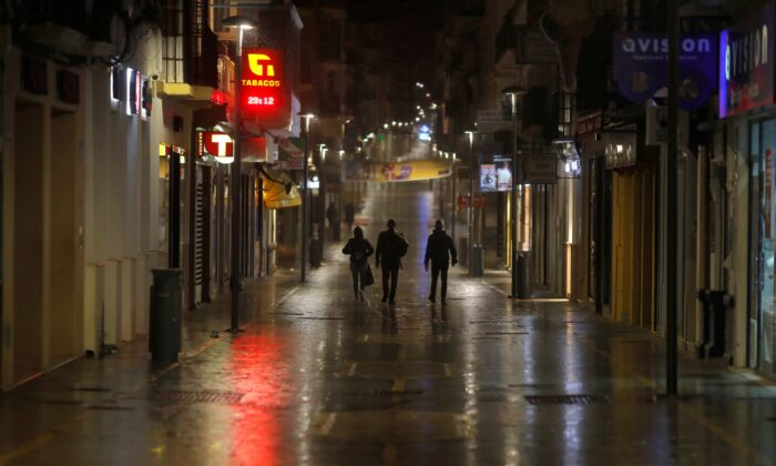 People walk along an empty street during the first day of the night-time curfew set as part of a state of emergency in an effort to control the outbreak of the coronavirus disease (COVID-19), in downtown Ronda, Spain, on Oct. 25, 2020. (Jon Nazca/Reuters)