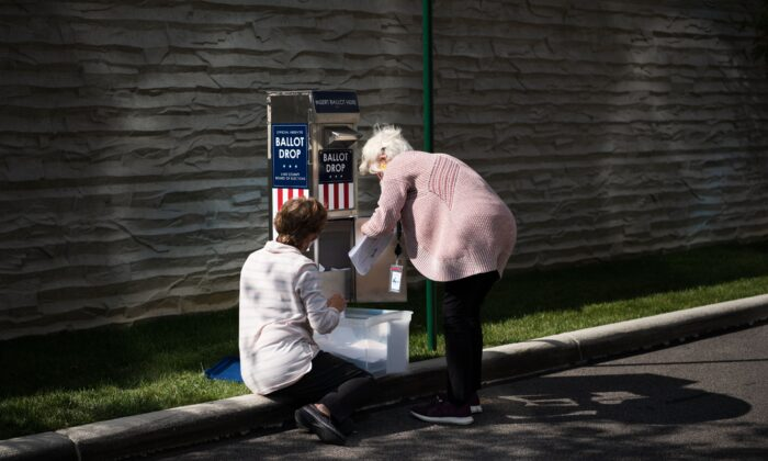 Two employees with the Lake County Board of Elections collect absentee ballots from a dropbox outside election headquarters in Painesville, Ohio on Oct. 16, 2020. (DUSTIN FRANZ/AFP via Getty Images)