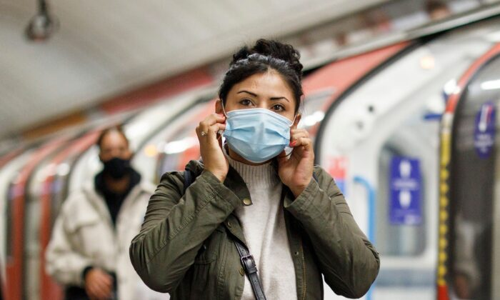 Commuters wear face-masks during the morning rush hour on the Victoria Line of the London Underground in central London on Oct. 16, 2020, (Tolga Akmen /AFP/Getty Images)