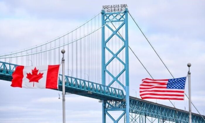 Canadian and American flags fly near the Ambassador Bridge at the Canada/USA border crossing in Windsor, Ont. on March 21, 2020. (The Canadian Press/Rob Gurdebeke)