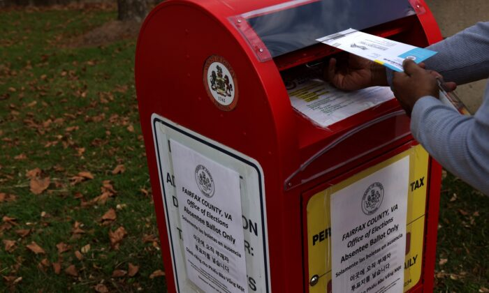 A voter drops an absentee ballot for the Nov. 3 election into a collecting bin outside Fairfax County Government Center in Fairfax, Va. on Oct. 19, 2020. (Alex Wong/Getty Images)