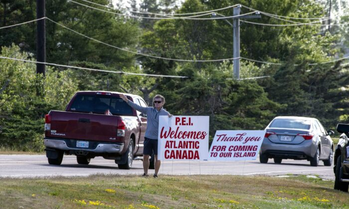 A Charlottetown businessman representing a group of 25 business people welcomes visitors from within the Atlantic bubble to the province near Borden-Carleton, P.E.I., on July 7, 2020. (The Canadian Press/Brian McInnis)