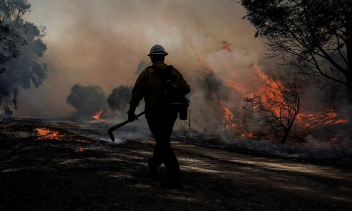 A firefighter prepares to put out hotspots while battling the Silverado Fire in Irvine, Calif., on Oct. 26, 2020. (Jae C. Hong/AP Photo)