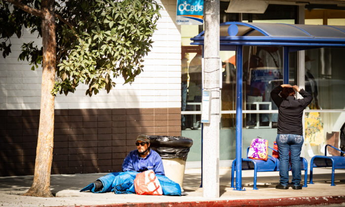 A homeless man sits on the sidewalk near a bus shelter in Costa Mesa, Calif., on Oct. 26, 2020. (John Fredricks/The Epoch Times)