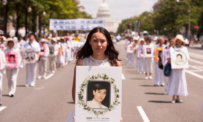 A woman holds a photo of a man killed by the Chinese regime in its persecution of Falun Gong, during a parade in Washington on July 17, 2014. (Larry Dye/The Epoch Times)