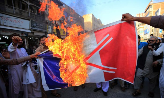 Pakistanis burn a French national flag during a protest following French President Emmanuel Macron's comments over the Mohammed caricatures, in Peshawar, on Oct. 26, 2020. (Abdul Majeed/AFP via Getty Images)