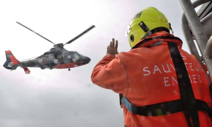 A French SNSM (Societe National de Sauvetage en Mer) lifeboat man waves to a helicopter of the French Navy during a rescue off the coast of Calais, France, on July 4, 2013. (Denis Charlot/AFP via Getty Images)