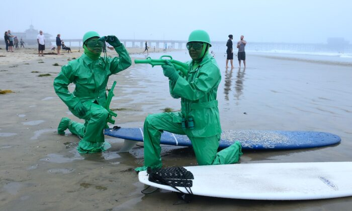 "Surfers dressed as the green soldiers from ""Toy Story,"" Irma Perez (L) and Susan Janechek (R), strike a pose at the annual Blackie's Halloween Surfing event in Newport Beach, Calif., on Oct. 27, 2018. The 2020 event will be held on Oct. 31. (Frederic J. Brown/AFP via Getty Images)"