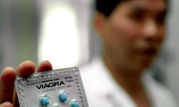 A Chinese doctor shows the anti-impotence drug Viagra at a hospital in Shanghai on July 5, 2000. (Liu Jin/AFP via Getty Images)