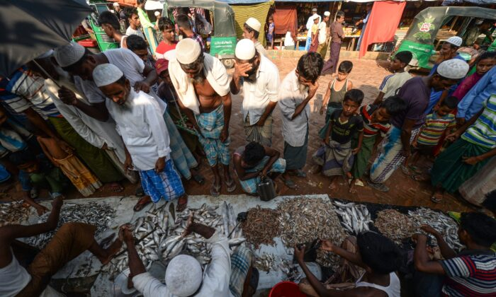 Rohingya refugees buy fish at a market place in Kutupalong refugee camp in Ukhia on Oct. 8, 2020. (Munir Uz zaman/AFP via Getty Images)