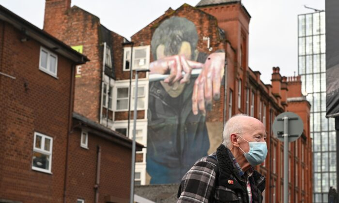 A man walks past a mural painted as part of the Cities of Hope festival in 2016 and highlighting mental health, in Ancoats, northern Manchester, England, on Oct. 16, 2020. (Oli Scarff/AFP via Getty Images)