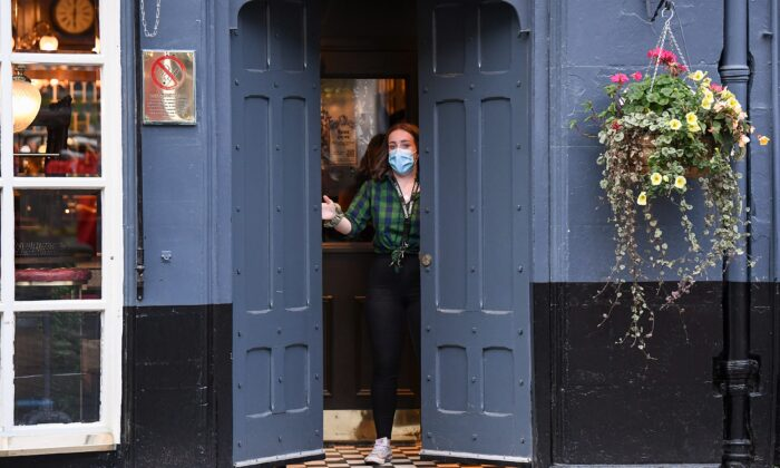 A member of staff closes a door of The Beehive pub in the Grassmarket following last orders at 6pm, in Edinburgh, Scotland, on Oct. 9, 2020. (Jeff J Mitchell/Getty Images)