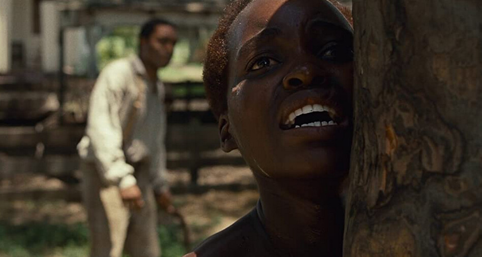 "black man with horsewhip and female slave tied to tree in ""12 Years a Slave"""