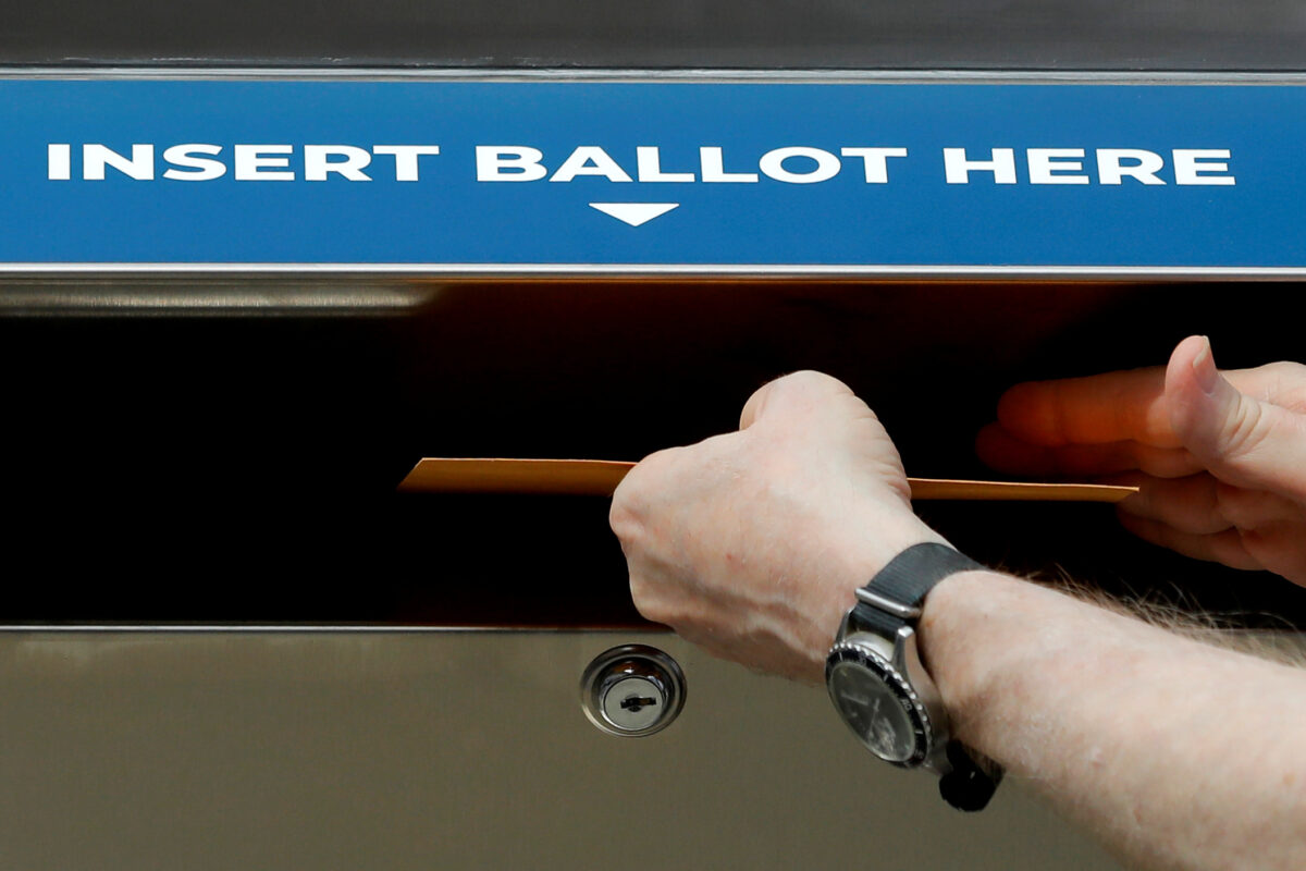 person inserting a ballot into drop box