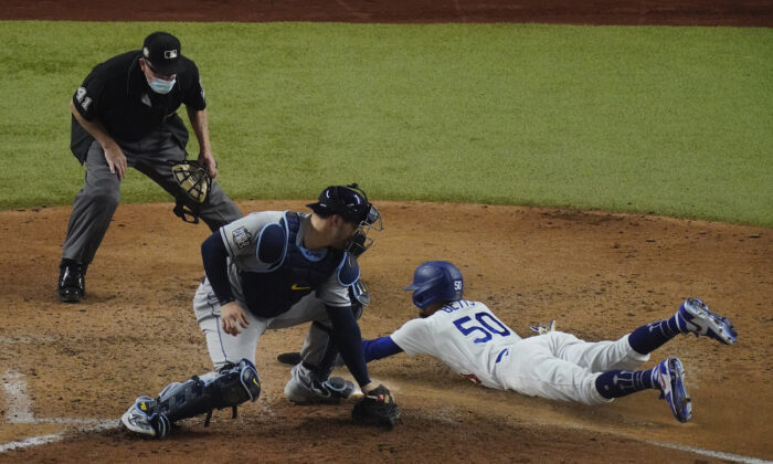 Los Angeles Dodgers' Mookie Bettscs scores past Tampa Bay Rays catcher Mike Zunino during the sixth inning in Game 6 of the baseball World Series, in Arlington, Texas, Oct. 27, 2020. (AP Photo/Sue Ogrocki)