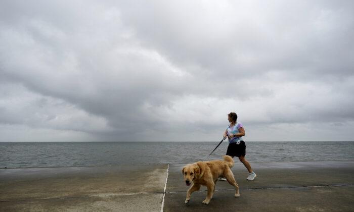 Jane McDow walks with her dog 'Duke' along the Lake Pontchartrain seawall in New Orleans, on Oct. 28, 2020. (Gerald Herbert/AP)
