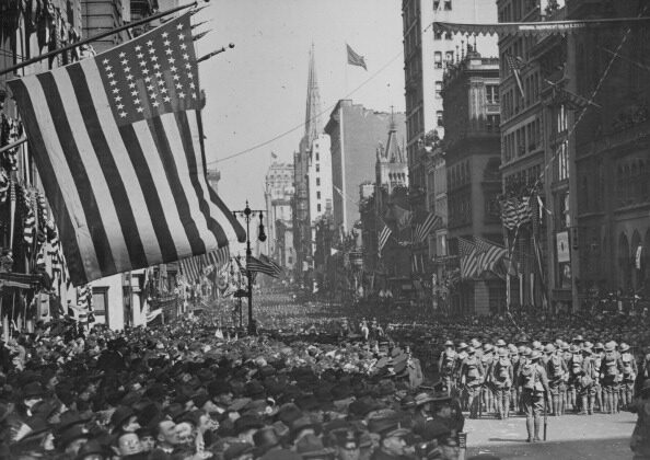 A military parade with crowds of excited spectators along New York's Fifth Avenue, in celebration of Armistice Day following World War I, November 1918. (Paul Thompson/FPG/Getty Images)