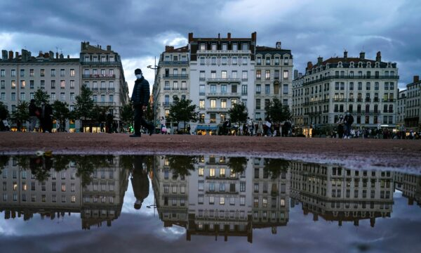 A man wearing a mask walks in the street in the center of Lyon