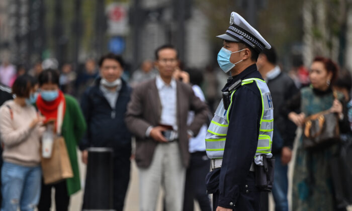 A police officer wearing a face mask monitors pedestrian traffic along a street in Shanghai on Oct. 28, 2020. (Hector Retamal/AFP via Getty Images)