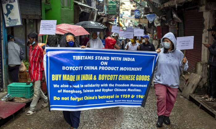 Exiled Tibetans hold placards during a protest march in support of the boycott of Chinese-made goods, in Dharmsala, India, on July 21, 2020. (AP Photo/Ashwini Bhatia)