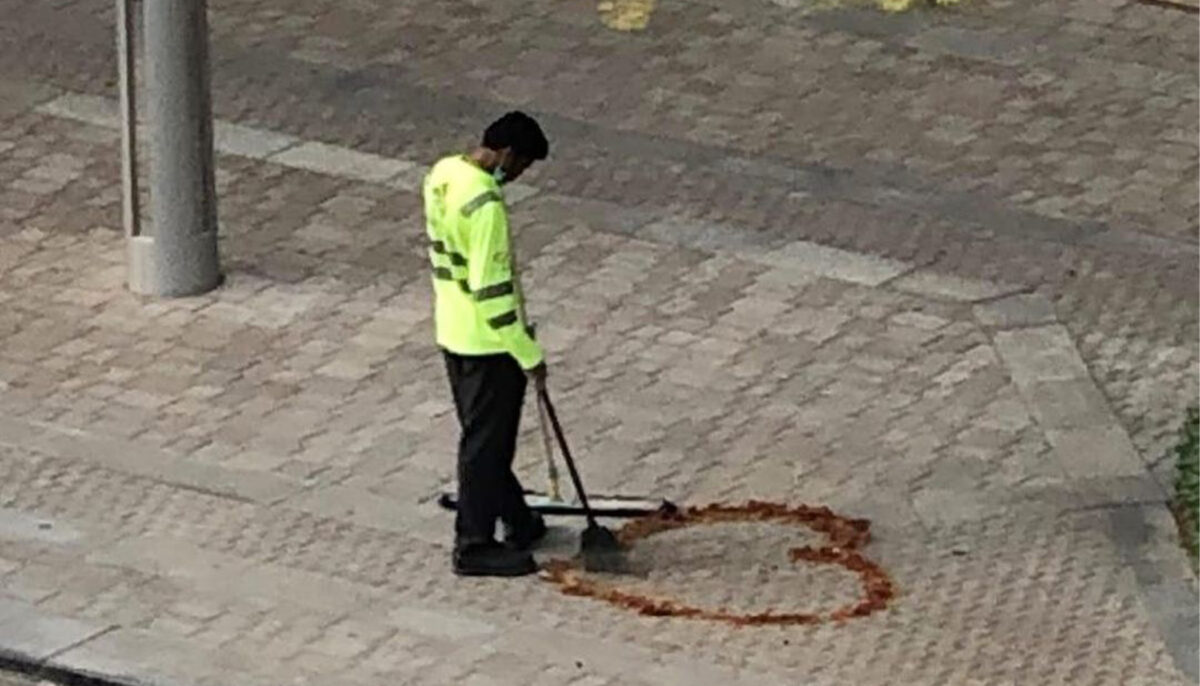 Cleaner draws heart on sidewalk with leaves amid...