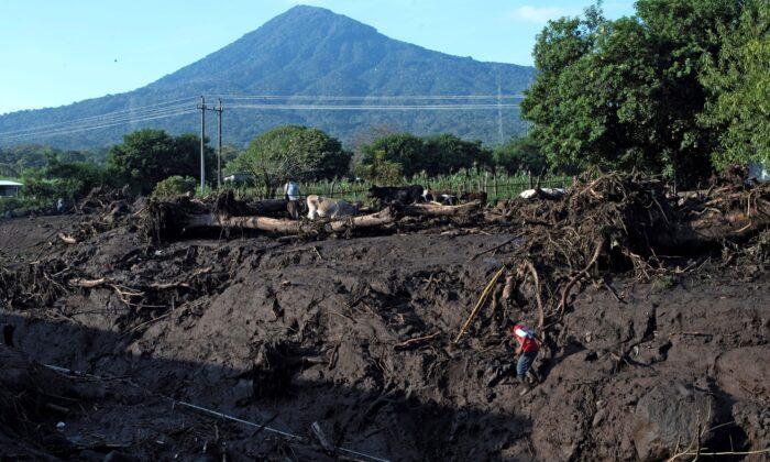 A resident descends a riverbank left after a landslide near the San Salvador volcano in Nejapa, El Salvador, on Oct. 30, 2020. (Yuri Cortez/AFP via Getty Images)