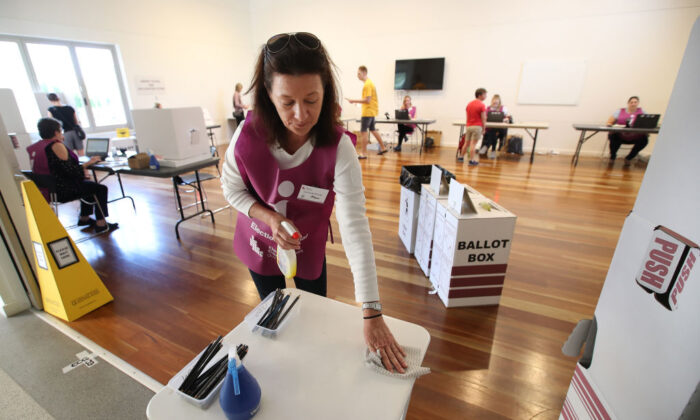An election official sanitizes a table at a polling booth on March 28, 2020 in Brisbane, Australia. (Jono Searle/Getty Images)