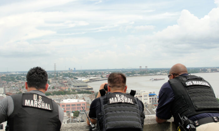 U.S. Marshals stand on a building as they look out toward the city in a file photo. (Illustration - Elliott Cowand Jr/Shutterstock)