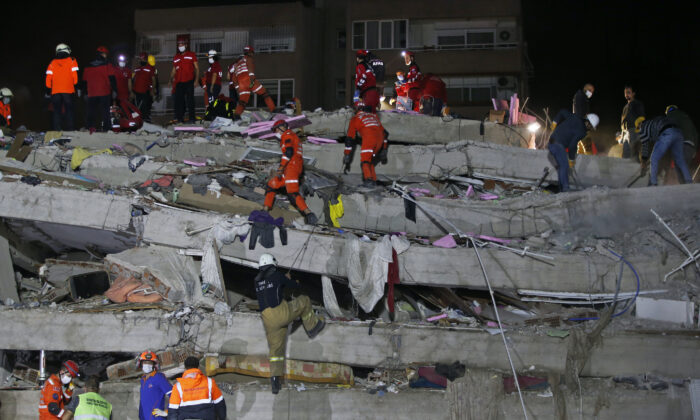 Members of rescue services search in the debris of a collapsed building for survivors in Izmir, Turkey, on Oct. 31, 2020 (Emrah Gurel/AP Photo)