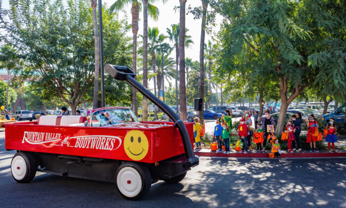 A car decorated as a giant red wagon passes by costumed children at the 14th annual Fountain Valley Hospital Trick-or-Treat Parade in Fountain Valley, Calif., on Oct. 30, 2020. (John Fredricks/The Epoch Times)